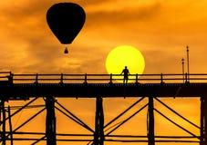 现出轮廓漂浮在sangklaburi,日落的泰国的老木桥的热空气气球 免版税库存图片