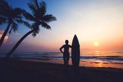 现出轮廓热带海滩的女子冲浪者在日落 库存图片