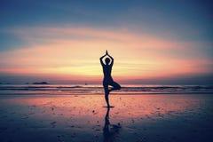 现出轮廓瑜伽海和日落的背景的凝思女孩 免版税库存图片