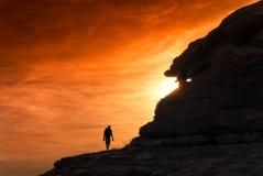 现出轮廓的远足者走入灼烧的天空日落 图库摄影