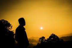 现出轮廓站立在上面的一个人的图象小山 日落日出 图库摄影