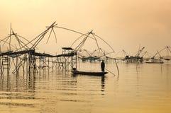 现出轮廓站立在小船, Patthalung,泰国的人 库存照片