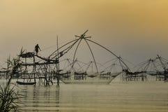 现出轮廓站立在捕鱼设备, Patthalung, Thail的人 图库摄影