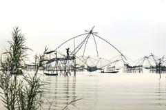 现出轮廓站立在捕鱼设备, Patthalung, Thail的人 免版税图库摄影