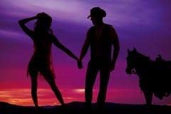 现出轮廓纯粹礼服的妇女有牛仔和马的 库存照片