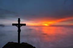 现出轮廓耶稣和十字架在被弄脏的日落 免版税库存图片