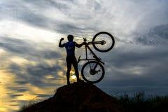 现出轮廓行动举的自行车的人在他的顶头立场上 库存照片