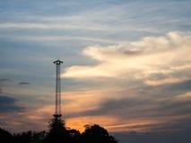 现出轮廓象飞碟的聚光灯杆与日落和多云backgr 免版税库存图片