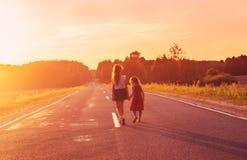 现出轮廓走在路的两个小女孩 姐妹enjoye 免版税图库摄影