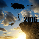 现出轮廓跳伞运动员飞将军着陆对新年2016年 库存图片