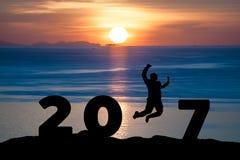 现出轮廓跳跃在海和2017年的商人,当庆祝新年时 库存照片