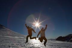 现出轮廓跳跃在雪的夫妇反对太阳和蓝天 免版税库存照片