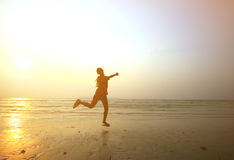 现出轮廓跳跃用手的女孩在海滩 库存图片