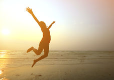 现出轮廓跳跃用手的女孩在海滩 免版税图库摄影