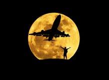 现出轮廓身分被上升胳膊庆祝在飞机期间从有大满月的跑道离开的人 图库摄影
