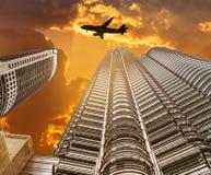 现出轮廓登陆在现代摩天大楼的飞机飞行 库存图片