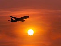 现出轮廓飞行到在日落的天空的乘客飞机 免版税库存照片