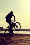 现出轮廓骑自行车者,年轻人,在日落靠近河,跃迁的,葡萄酒样式 库存图片