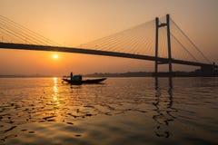现出轮廓Vidyasagar桥梁日落有一条小船的在河Hooghly 免版税图库摄影