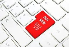 现在商店购买企业概念。红色购物车按钮或钥匙在白色键盘 免版税库存照片