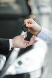 现在这辆汽车是你的。给钥匙的汽车推销员新的加州 库存照片