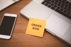 现在`顺序在柱子纸的`文本在膝上型计算机和巧妙的电话附近在木桌、网上购物和技术行销上概念 简单程序设计语言 库存照片