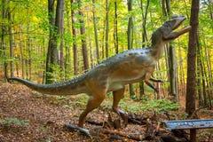 现实恐龙模型在森林里 免版税库存照片