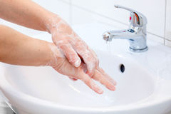 现有量洗涤物与肥皂的在自来水之下 免版税库存照片
