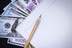现金、纸片和铅笔 免版税库存照片
