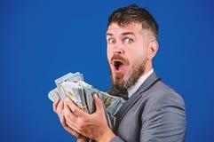 现金交易事务 人愉快的优胜者富有的举行堆美元钞票蓝色背景 容易的现金贷款 库存照片