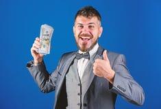 现金交易事务 人愉快的优胜者富有的举行堆美元钞票蓝色背景 o ?? 库存图片