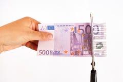现金后面的概念 剪刀切开了钞票500欧元题字现金后面 免版税库存图片