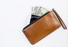现金和智能手机在棕色皮革钱包里 库存照片