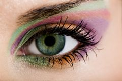 现代一只女性眼睛的时尚绿色紫罗兰色构成-宏观射击 图库摄影