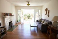 现代休息室内部有开放法语的Windows对庭院 免版税图库摄影