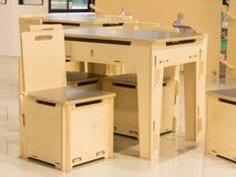 现代儿童的游戏室:木被设置的桌和椅子 库存图片