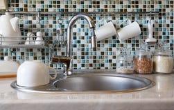 现代内部的厨房 厨房龙头、水槽和各种各样的陶瓷白色盘 免版税库存图片