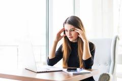 现代办公桌的年轻可爱的妇女,研究膝上型计算机,按摩寺庙忘掉恒定的头疼 免版税库存照片