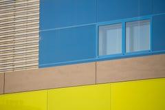 现代办公楼。五颜六色的大厦在一个工业地方。蓝色和黄色窗口。 免版税库存图片