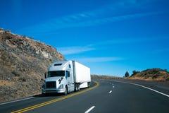 现代半卡车和拖车在转动岩石有风路 库存图片