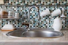 现代厨具和器物包括杯子、杯子、茶罐和瓶子用谷物在轻拍和水槽附近 免版税库存照片