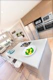 现代厨房内部和果子在桌上在豪华h 免版税库存照片