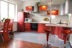 现代厨房内部有一个酒吧柜台的在红色口气 免版税图库摄影