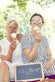 现代吃冰淇凌的妈妈和年轻女儿 免版税库存照片