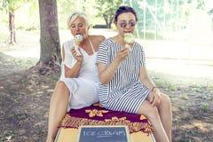 现代吃冰淇凌的妈妈和年轻女儿 库存照片