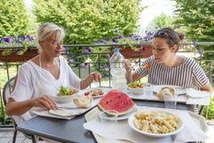 现代吃午餐的妈妈和年轻女儿 库存图片