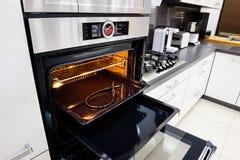 现代喂tek厨房,与开放的门的烤箱 库存照片