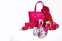 现代妇女` s桃红色袋子、钱包、凉鞋和围巾在白色背景 图库摄影