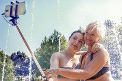 现代妈妈和年轻女儿采取selfie 图库摄影