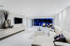现代客厅在与沙发和枕头的晚上 免版税库存照片